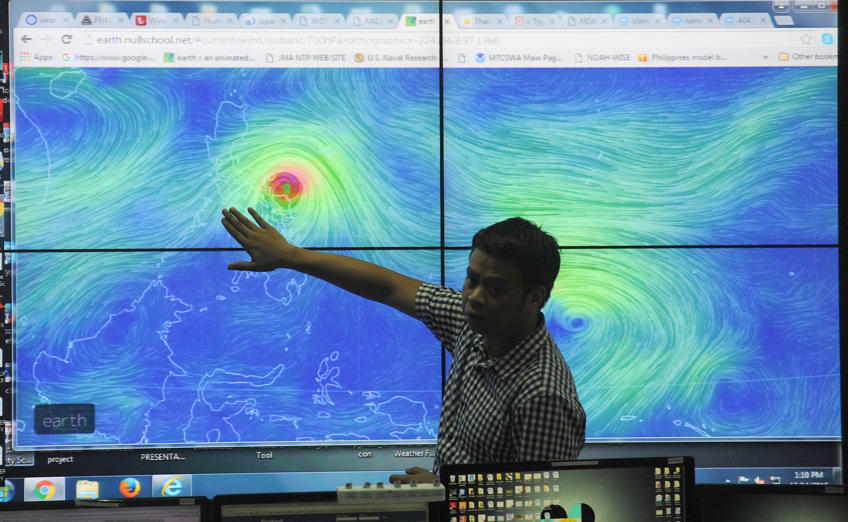 Meteorologists from the Philippine Atmospheric Geophysical and Astronomical Services Administration (PAGASA) monitor and plot the direction of powerful Typhoon Melor at their headquarters in suburban Manila on December 14, 2015. More than 700,000 people fled the central Philippines amid threats of giant waves, floods and landslides as powerful Typhoon Melor approached the archipelago nation, officials said on December 14.