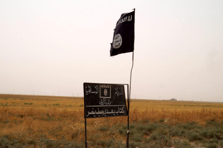 Islamic State group's flag is seen in an area after Kurdish troops known as peshmerga regained control of some villages west of the oil-rich city of Kirkuk, 180 miles (290 kilometers) north of Baghdad, Iraq, Wednesday, Sept. 30, 2015.