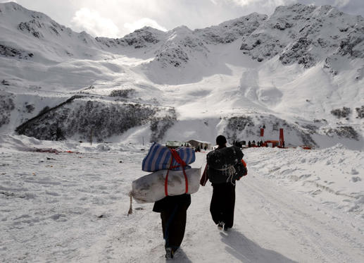BOME, Dec. 15, 2010 (Xinhua) -- Two bearers walk ahead to Medog by walking through Galung La Tunnel on the highway linking Bome and Medog in southwest China's Tibet Autonomous Region for the first time, Dec. 15, 2010.