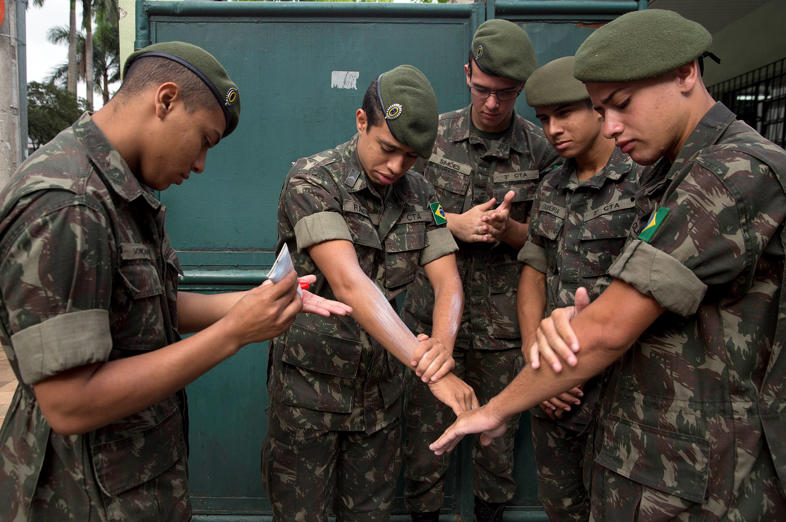 Army soldiers apply insect repellent as they prepare for a clean up operation against the Aedes aegypti mosquito, which is a vector for transmitting the Zika virus in Sao Paulo, Brazil, Wednesday, Jan. 20, 2016.  A U.S. warning urging pregnant women to avoid travel to Latin American countries where the mosquito-borne virus is multiplying threatens to depress tourism to the region, one of its few bright spots at a time of deep economic pain. (AP Photo/Andre Penner)