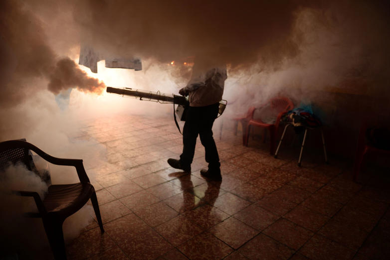 TOPSHOT - A Health Ministry employee fumigates a home against the Aedes aegypti mosquito to prevent the spread of the Zika virus in Soyapango, six km east of San Salvador, on January 21, 2016. Health authorities have issued a national alert against the Aedes Aegypti mosquito, because of the link between the Zika virus and microcephaly and Guillain-Barré Syndrome in fetuses. AFP PHOTO/Marvin RECINOS / AFP / Marvin RECINOS        (Photo credit should read MARVIN RECINOS/AFP/Getty Images)