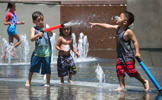 Children cool off at the water fountain in Grand Park, downtown Los Angeles,California on June 30, 2015.