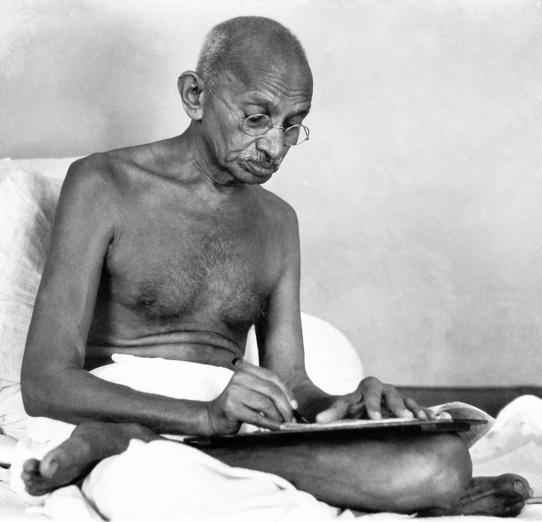Indian statesman and activist Mohandas Karamchand Gandhi (1869 - 1948) writing at Birla House, Mumbai, August 1942. (Photo by Dinodia Photos/Getty Images)