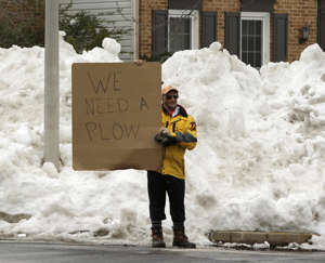 Mike Mazza stands outside of his subdivision attempting to get plow service for snowy streets in Gaithersburg, Maryland January 26, 2016. Washington will need several more days to return to normal after a weekend blizzard dropped more than 2 feet (60 cm) of snow along the U.S. East Coast, likely causing billions of dollars in damage and killing more than 30 people.