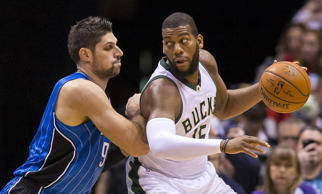 Jan 26, 2016; Milwaukee, WI, USA; Milwaukee Bucks center Greg Monroe (15) dribbles the ball as Orlando Magic center Nikola Vucevic (9) defends during the first quarter at BMO Harris Bradley Center.