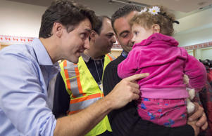 Canadian Prime Minister Justin Trudeau greets 16-month-old Madeleine Jamkossian, right, and her father Kevork Jamkossian, refugees fleeing the Syrian civil war, during their arrival at Pearson International airport, in Toronto, on Friday, Dec. 11, 2015.