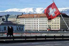 GENEVA, SWITZERLAND - FEBRUARY 09: A Swiss flag flies above a HSBC logo is seen on HSBC offices on February 9, 2015 in Geneva, Switzerland. It has been discovered that the HSBC bank has helped wealthy clients to evade tax in several countries across the world, including the UK, America, France and Belgium. (Photo by Harold Cunningham/Getty Images)