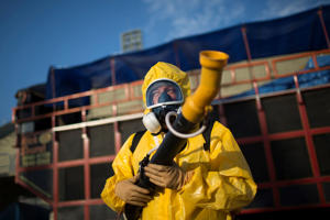 A health worker stands in the Sambadrome as he sprays insecticide to combat the Aedes aegypti mosquitoes that transmit the Zika virus, in Rio de Janeiro, Brazil, Tuesday, Jan. 26, 2016.  Inspectors began to spray insecticide around the Sambadrome, the outdoor grounds where thousands of dancers and musicians will parade during the city's Feb. 5-10 Carnival celebrations. Brazil's health minister says the country will mobilize some 220,000 troops to battle the mosquito blamed for spreading a virus linked to birth defects.