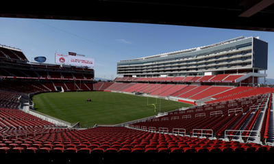 FILE - In this July 17, 2014, file photo, a groundskeeper drives across the field before the ribbon-cutting and opening of Levi's Stadium in Santa Clara, Calif. When the architects set out to design a new football stadium for the San Francisco 49ers, they wanted a building that fit the Silicon Valley region where it is located. Retro was out. High-tech and green-friendly were in.