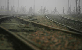 File: Commuters walk across railway tracks amid heavy fog in New Delhi in this January 8, 2010 file photograph.