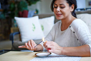 Woman lighting an incense stick at home.