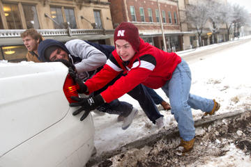 Cole White, right, gets help from Nawaf Khalaf and Kyle Hartley as they attempt to push a vehicle out of the snow on Feb. 2, 2016, in Lincoln, Neb.
