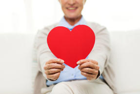 close up of senior woman with red heart at home