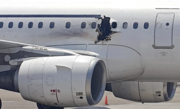 In this Tuesday, Feb. 2, 2016 photo, a hole is photographed in a plane operated by Daallo Airlines as it sits on the runway of the airport in Mogadishu, Somalia. A gaping hole in the commercial airliner forced it to make an emergency landing at Mogadishu's international airport late Tuesday, officials and witnesses said. AP Photo