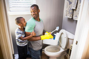 Man with son, cleaning bathroom toilet
