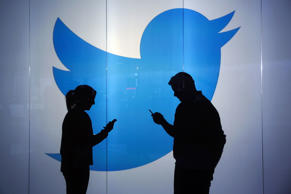 People are seen as silhouettes as they check mobile devices while standing wall bearing Twitter Inc.'s logo in this arranged photograph in London, U.K., on Jan. 5, 2016.