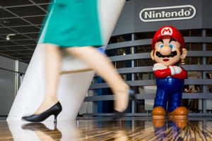 "A woman walks past a figure of ""Mario"", a character in Nintendo's ""Mario Bros."" video games, at a Nintendo centre in Tokyo July 29, 2015."