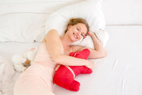 Woman lying on bed holding toy.