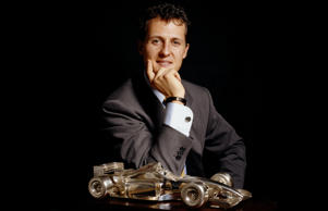 German motor racing champion Michael Schumacher posing with a glass replica of his Formula 1 Grand Prix car. (Photo by Terry O'Neill/Getty Images)