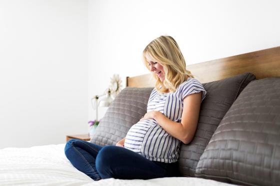 Бременна жена докосва корема
