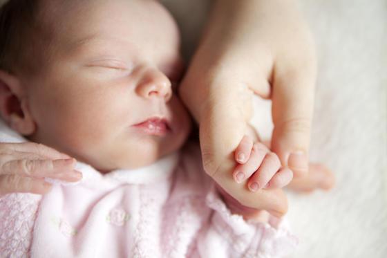 Новородено бебе държеше ръката на майка си