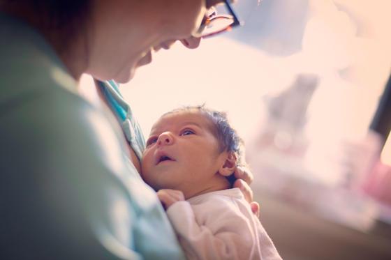 Мама гледа новородено в болница