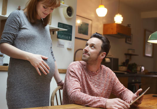Бременна жена и партньор у дома