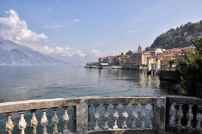 [UNVERIFIED CONTENT] The town of Bellagio on the Como Lake, in the foreground with a marble balustrade, where is possible to rest and admire the lake In the background the clouds cover the peaks of the Alps, in a beautiful day in April