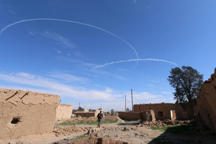 A Syria Democratic Forces fighter walks under contrails made by U.S. alliance air forces on the outskirts of al-Shadadi town, Hasaka countryside, Syria February 19, 2016.