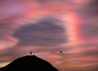 A man stands on top of a hill as ice particle iridescence is seen in high-level Nacreous clouds on February 02, 2016 in Saltburn-by-the-Sea, England. The rare effect is caused by the diffraction of sunlight in the ice crystals that form the Nacreous clouds at high altitudes.