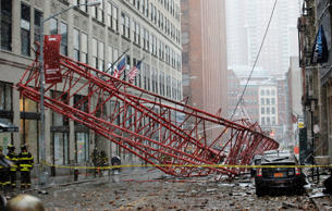 Emergency crews survey a massive construction crane collapse on a street in down...