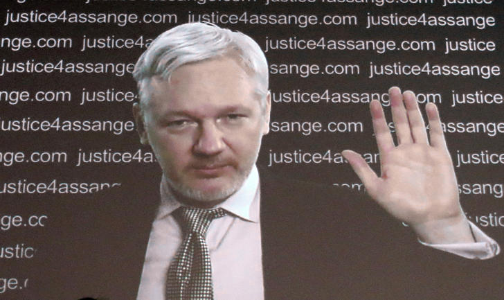 "WikiLeaks founder Julian Assange is seen on a screen as he addresses the media from the London embassy of Ecuador Friday Feb. 5, 2016, where he has been holed up for some 3½ years to avoid extradition to Sweden for questioning about alleged sexual offenses. A U.N. human rights panel says Assange has been ""arbitrarily detained"" by Britain and Sweden since December 2010. The U.N. Working Group on Arbitrary Detention said his detention should end and he should be entitled to compensation."