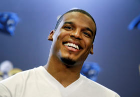 Carolina Panthers quarterback Cam Newton smiles as he answers questions during a...