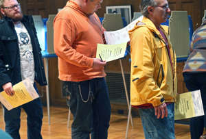 1.	A man, center, studies his ballot as he and fellow voters wait in line to place their ballots, Nov. 4, 2014, in Minneapolis.
