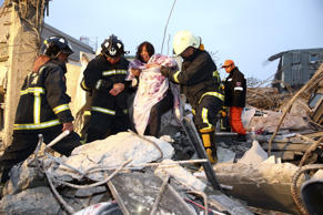 Rescue personnel help a victim at a damaged building after an earthquake in Tain...