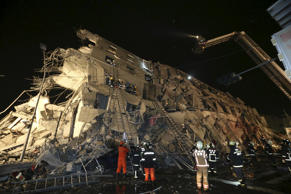 Rescue personnel work at a damaged building after an earthquake in Tainan, south...