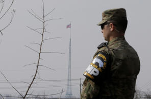 A North Korean flag flies in the propaganda village of Gijungdong as a U.S. Army soldier stands guard at Taesungdong freedom village near the border village of Panmunjom in Paju, South Korea, Thursday, Feb. 4, 2016.