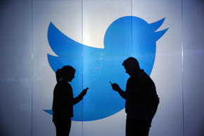 People are seen as silhouettes as they check mobile devices while standing against an illuminated wall bearing Twitter's logo in this arranged photograph in London, U.K., on Tuesday, Jan. 5, 2016.