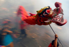 Dragon and lion dancers perform amidst exploding firecrackers in celebration of ...