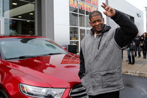 Detroit resident James Robertson waves to the crowd after being surprised with the free gift of a 2015 red Ford Taurus sedan, at the Suburban Ford dealership in Sterling Heights, Michigan, February 6, 2015