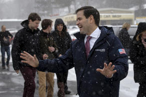 U.S. Republican presidential candidate Marco Rubio laughs in the snow as he depa...