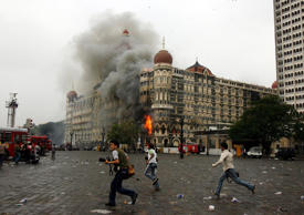 File: Photographers run past the burning Taj Mahal Hotel during a gun battle in Mumbai in this November 29, 2008 file photo.