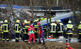 Firefighters and emergency doctors work at the site of a train accident near Bad Aibling, southern Germany, on February 9, 2016.