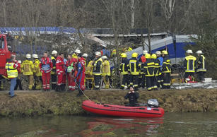 Rescue personell stand in front of two trains that crashed head on near Bad Aibling, southern Germany, Tuesday morning, Feb. 9, 2016. At least four people were killed in the crash. (AP Photo/Sebastian Stepniewski)