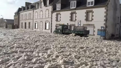 Video still of truck driving through sea foam in Penmarch, France.
