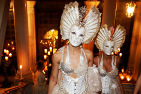 Masked performers wearing volto masks walk up the stairway at The Secret Garden ...