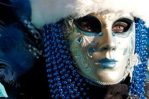A costumed reveller wearing a blue volto mask, decorated with blue beads, poses ...
