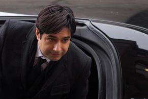 Former CBC radio host Jian Ghomeshi walks past protesters as he arrives at a Toronto court on Tuesday, Feb. 9, 2016.