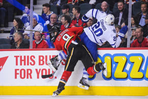 CALGARY, AB - FEBRUARY 9: Joe Colborne #8 of the Calgary Flames hits Frank Corrado #20 of the Toronto Maple Leafs during an NHL game at Scotiabank Saddledome on February 9, 2016 in Calgary, Alberta, Canada