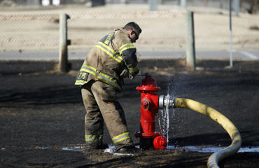 In this photo taken on Monday, Feb. 8, 2016, Broken Arrow Firefighter Derek Fulps closes a fire hydrant after his department battled a grass fire in a neighborhood in Broken Arrow, Okla. The fire burned through several yards but no homes were damaged.